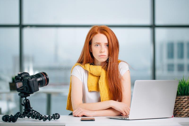 De droevige zitting van het roodharigemeisje vlogger bij lijst met laptop en het bekijken camera royalty-vrije stock afbeelding
