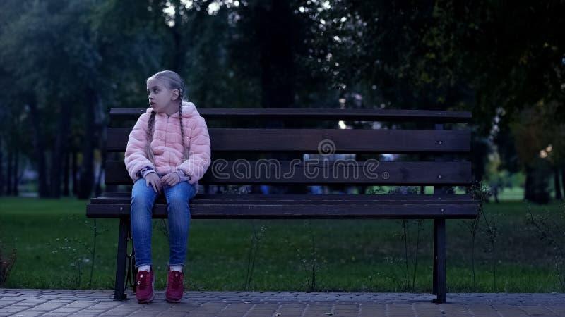 De droevige zitting van het schoolmeisje op bank in park, verloren het missen jong geitje, die op ouders wachten royalty-vrije stock afbeelding
