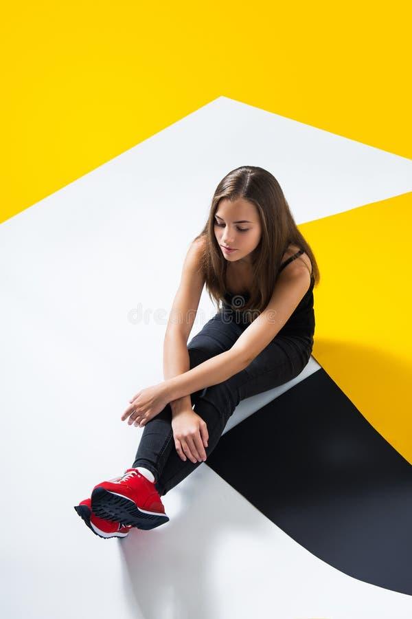 De droevige zitting van het tienermeisje op de vloer in de studio stock foto's
