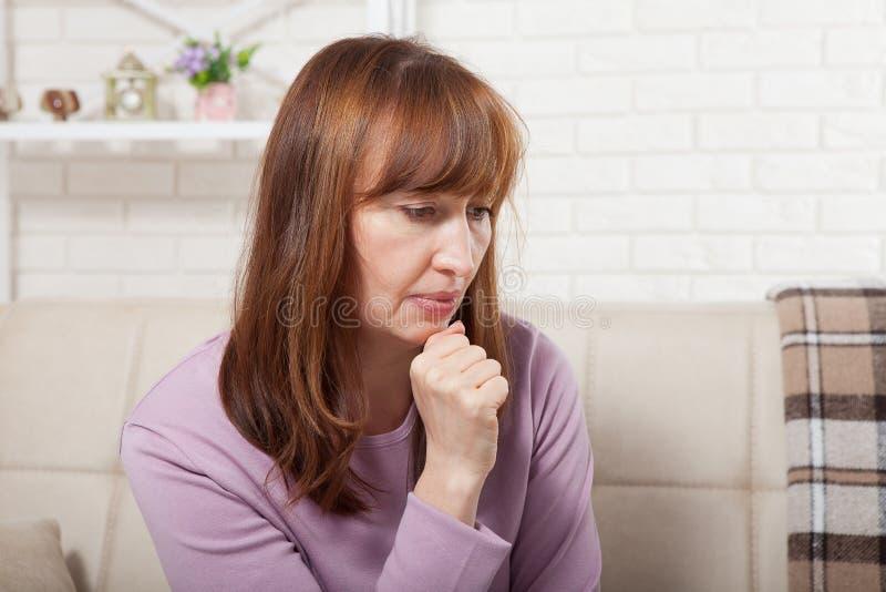 De droevige zitting van de middenleeftijdsvrouw op een bank in de woonkamer menopause stock afbeelding