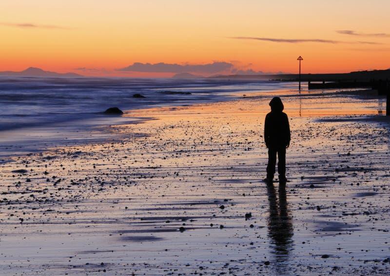 De droevige zonsondergang van het jongensstrand stock foto's