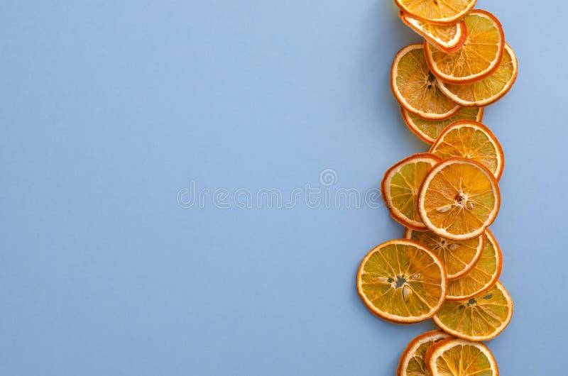 De droge citrusvruchten van plakkensinaasappelen op lichtblauwe achtergrond Eigengemaakt natuurlijk aromadecor Concept vakantie H royalty-vrije stock foto's