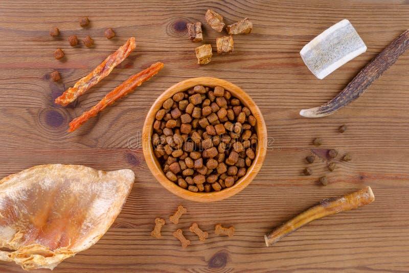 De droge hondevoer in een kom en de verschillende snack, kippenfilethaakwerk, geweitakken, long, oor op vlak wit, leggen stock foto's