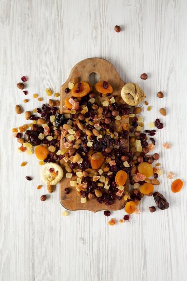 De droge vruchten en de noot mengen zich op rustieke houten raad over witte houten achtergrond, hoogste mening Close-up royalty-vrije stock foto's