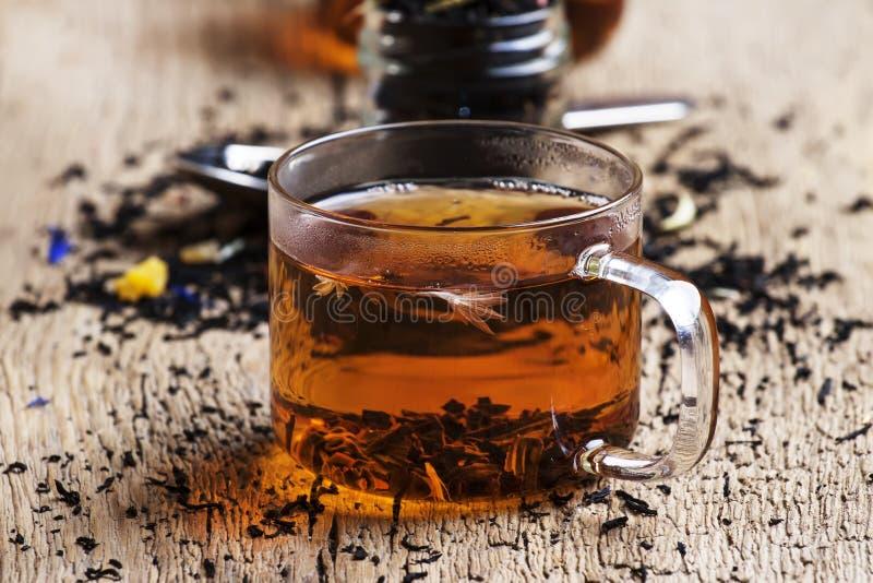 De droge zwarte thee van Ceylon met korenbloem blauwe bloemen en het gedroogd fruit, de uitstekende houten achtergrond van de keu royalty-vrije stock afbeelding