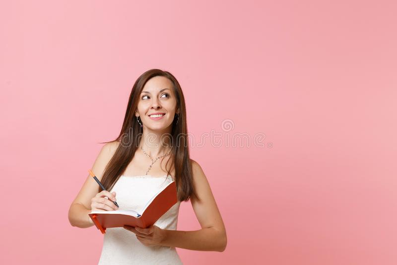 De dromerige bruidvrouw die in huwelijkskleding omhoog schrijft nota in notitieboekje planningshuwelijk het kiezen van personeels stock foto's