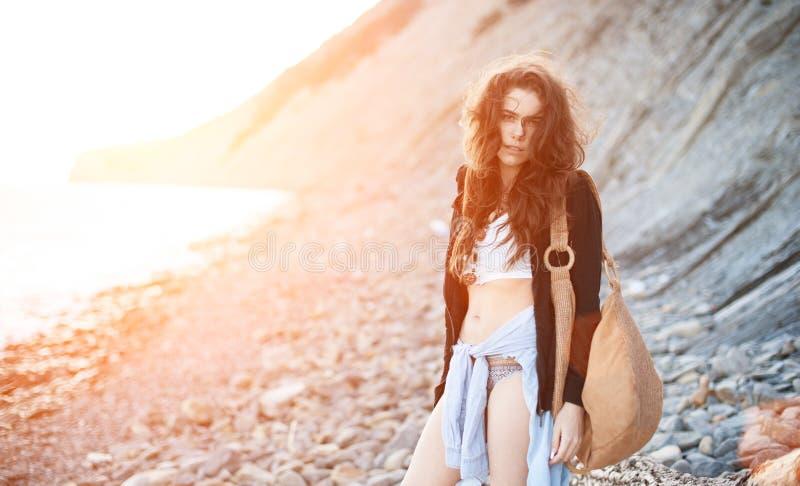 De dromerige eenzame donkerbruine hippie in de elegante stijl van bokho zit op grijze stenen bij de overzeese kust in de stralen  stock afbeelding
