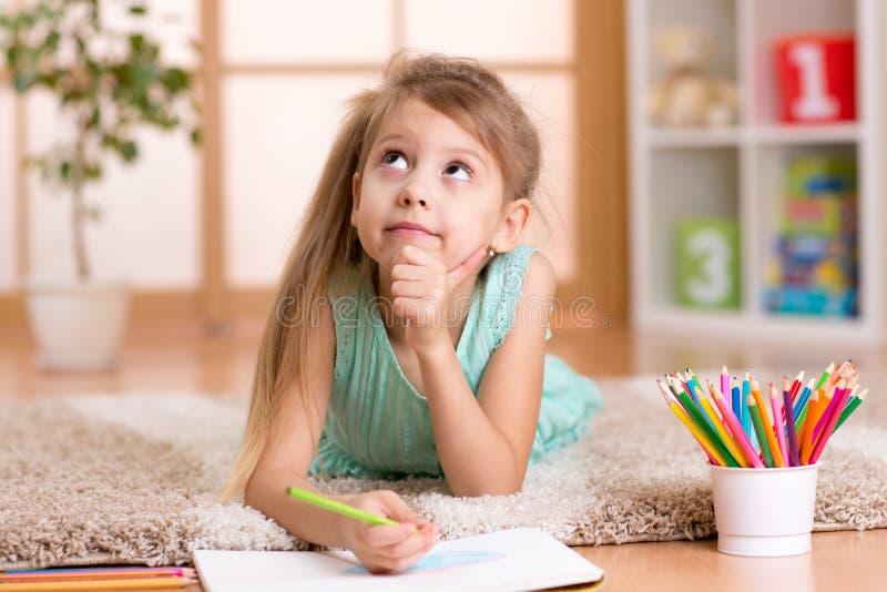 De dromerige tekening van het jong geitjemeisje met kleurenpotloden stock afbeelding
