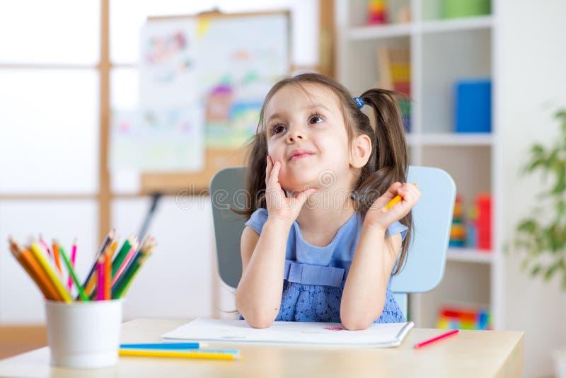 De dromerige tekening van het jong geitjemeisje met kleurenpotloden stock afbeeldingen