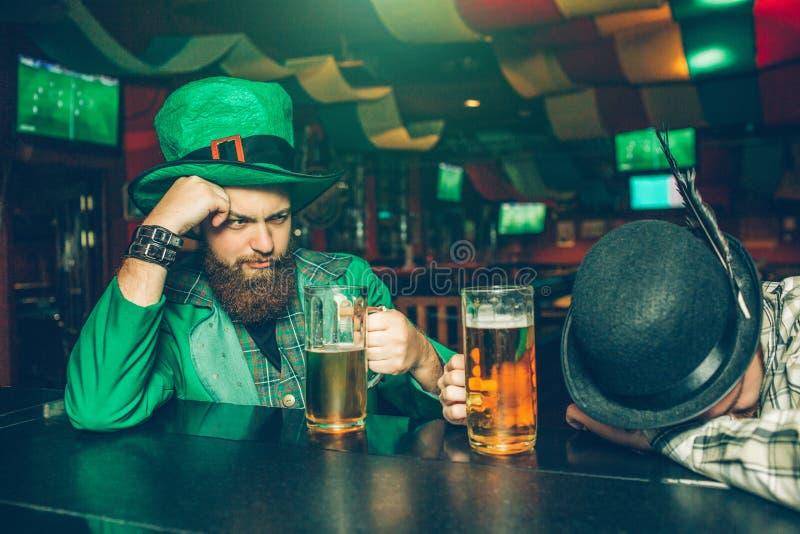 De dronken jonge mens in groen kostuum zit bij barteller in bar met vriend Een andere kerel viel in slaap Zij hebben mokken bier stock fotografie