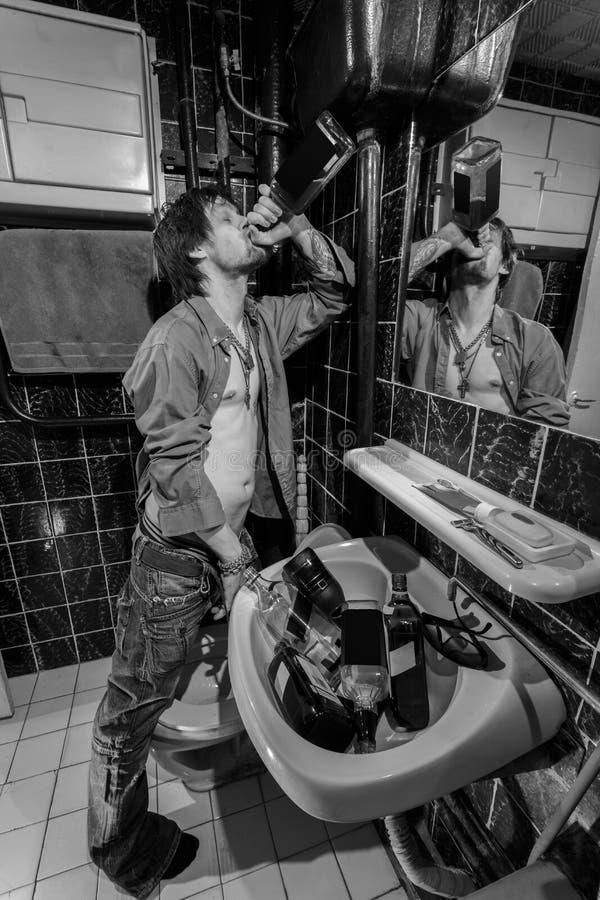 De dronken Mens bevindt zich in een toilet en drinkt whisky royalty-vrije stock fotografie