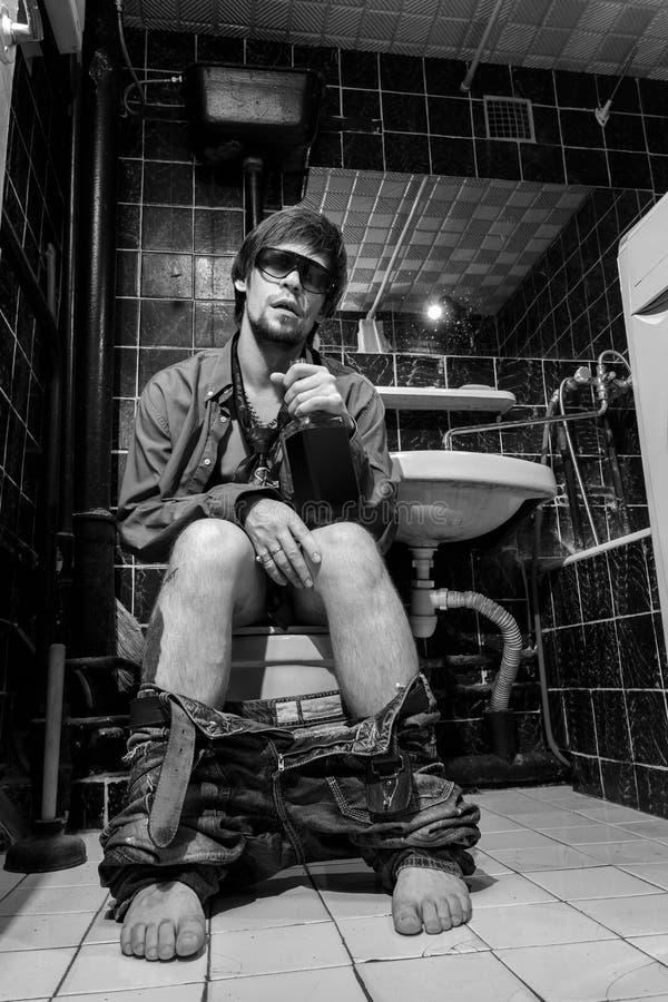 De dronken Mens zit in een toilet met een fles whisky stock afbeeldingen