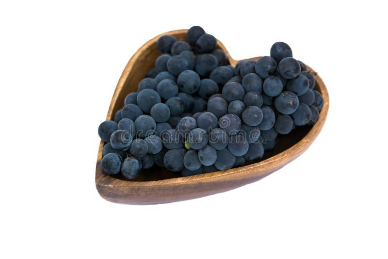 De druiven in een hart vormen houten plaat stock afbeelding
