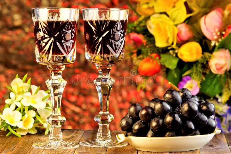 De druiven zijn een heerlijke delicatesse en een wijn in een glas op de achtergrond van van tuinbloemen en bokeh lichten vakantie royalty-vrije stock afbeelding