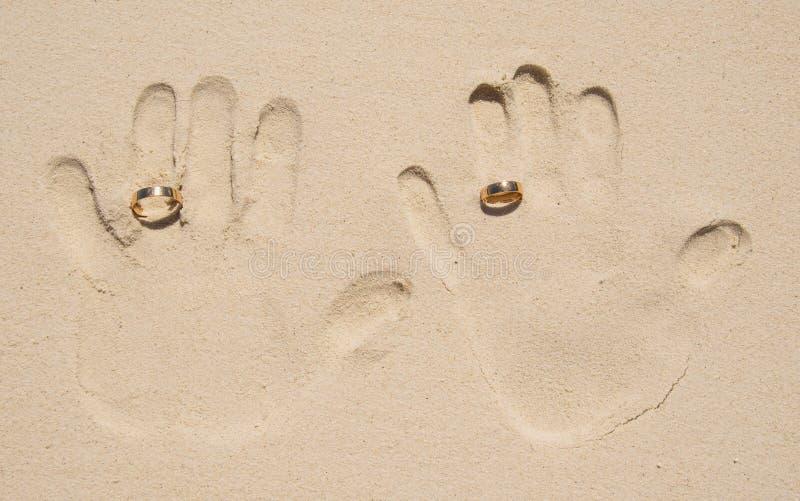 De druk van de echtpaarhand op zand stock afbeeldingen