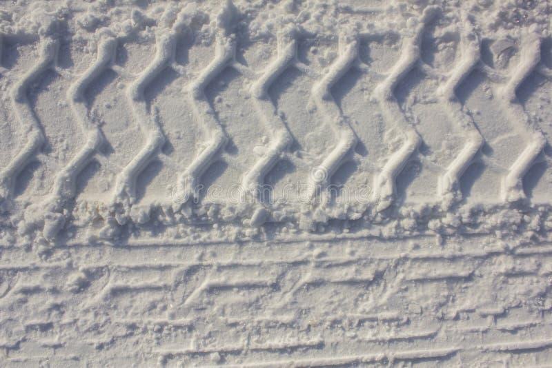 De drukken van de autoband op wit sneeuwclose-up Ruwe Oppervlaktetextuur stock fotografie