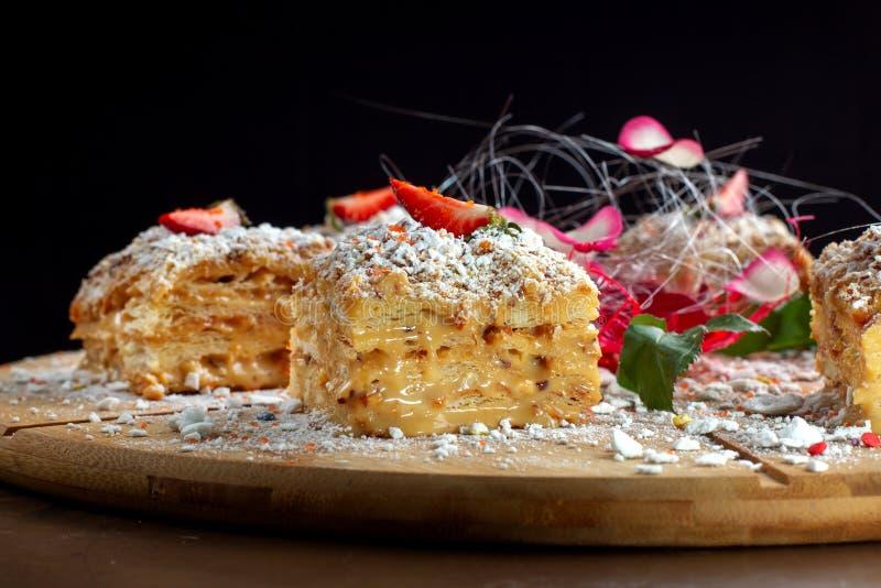 De duas partes do bolo Napoleon na bandeja de madeira Culin?ria do russo, bolo mergulhado com pastelaria cream-2 fotos de stock royalty free