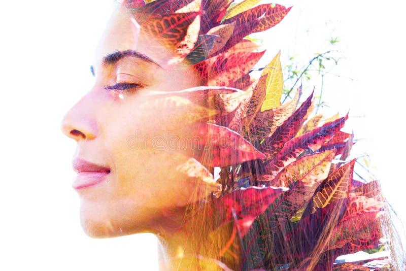 De dubbele blootstelling van het profiel van een gezonde natuurlijke schoonheid combineerde met rode en groene tropische bladeren royalty-vrije stock foto's