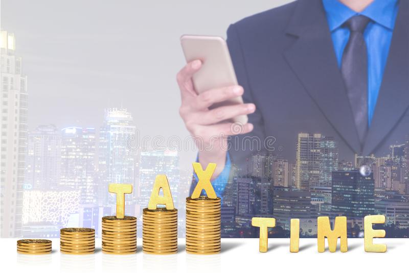 De dubbele blootstelling van stad en de zakenman die smartphone met muntstukken gebruiken stapelen en het woord van de belastings royalty-vrije stock fotografie