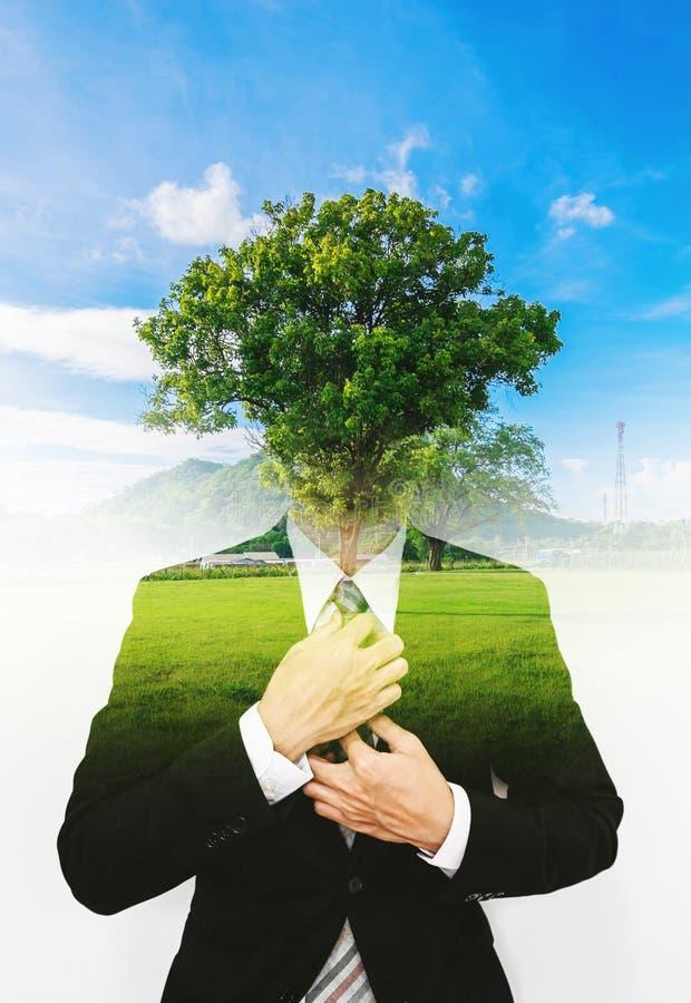 De dubbele blootstellingszakenman met een boom met blauwe hemel, ecologie vriendschappelijk concept, denkt Groen stock fotografie