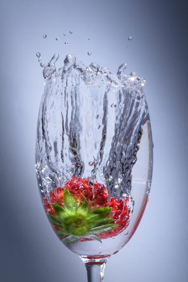 De duik van de aardbeiplons in water in een wijnglas stock foto