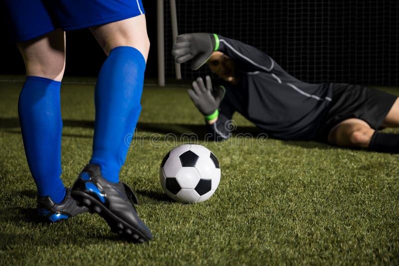 De duik van de voetbalkeeper om een doel tegen te houden stock afbeeldingen