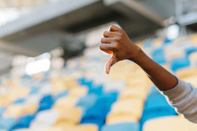 De duim neer op de hand van het Afro-Amerikaanse meisje bij de achtergrond van de stadionzetels royalty-vrije stock foto's