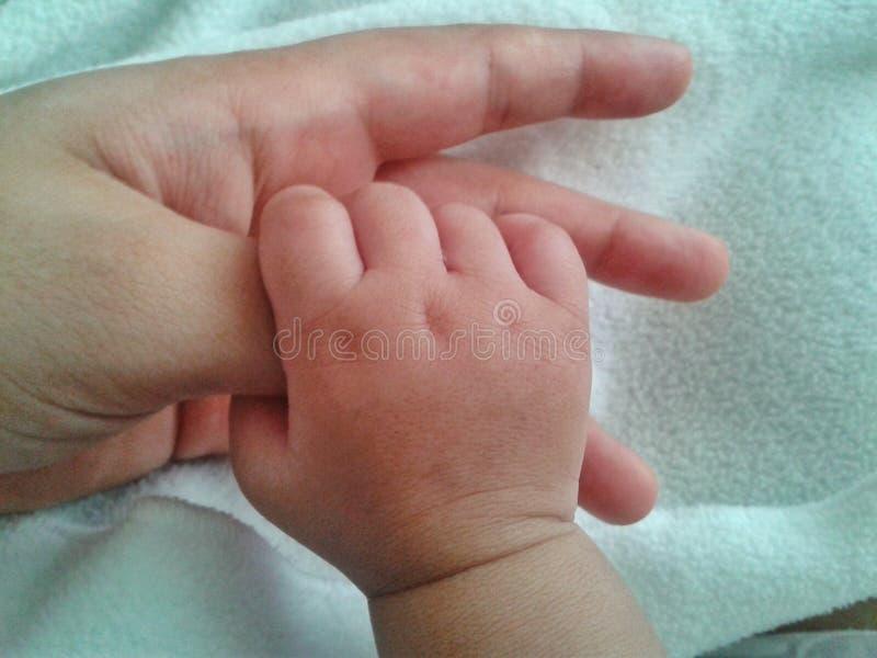 De duim van de holdingsmoeders van de baby stock afbeeldingen