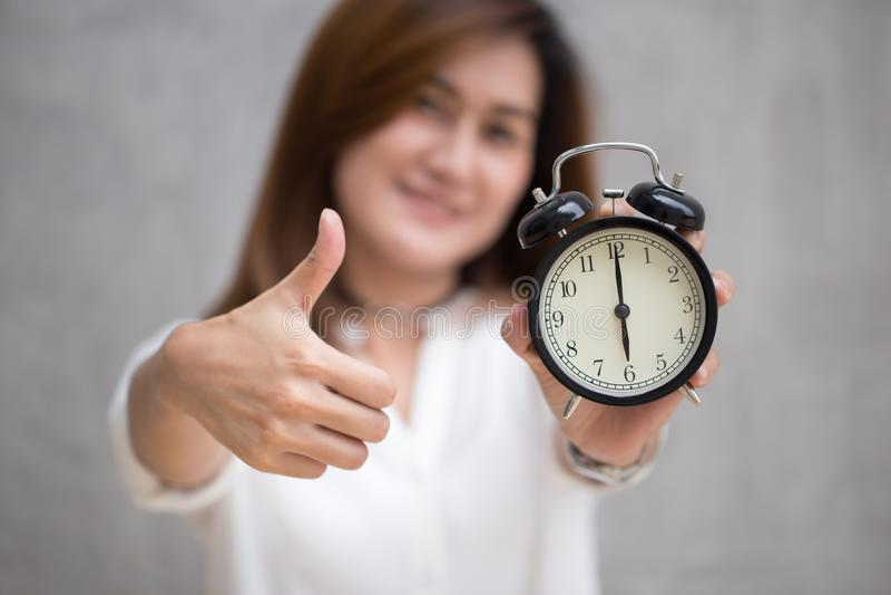De duimen met een klok voor goed tijd of goed beëindigen op tijd omhoog baanconcept royalty-vrije stock afbeelding