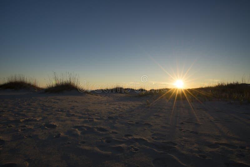 De duinen kleurrijke hemel van het kustzand bij zonsondergang stock afbeelding