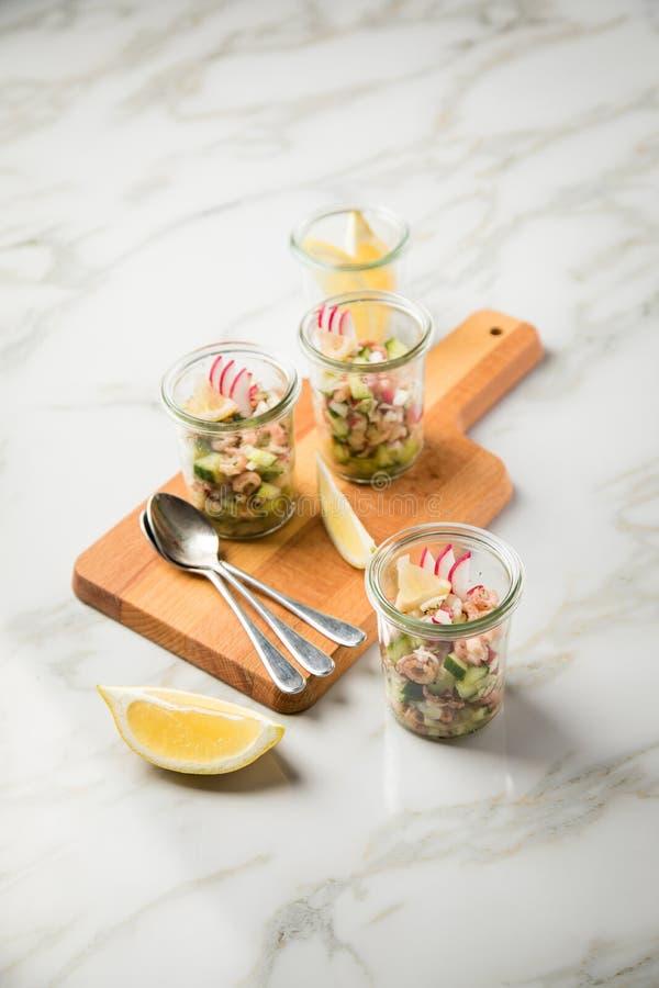 De Duitse salade van de Noordzee bruine garnalen van Friesland in glasmok met komkommer, rode radijs, dille en citroen op houten  royalty-vrije stock fotografie