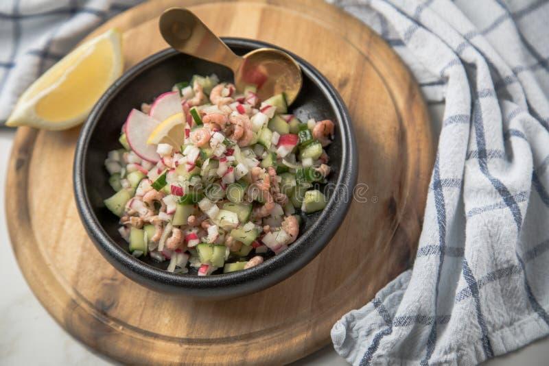 De Duitse salade van de Noordzee bruine garnalen van Friesland in kom met komkommer, rode radijs, dille en citroen op houten raad stock foto