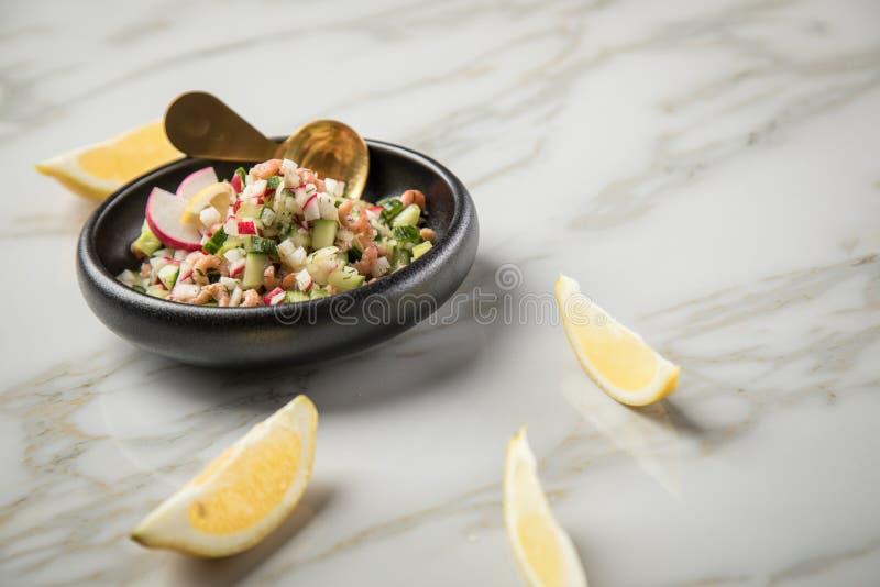 De Duitse salade van de Noordzee bruine garnalen van Friesland in kom met komkommer, rode radijs, dille en citroen op marmeren li royalty-vrije stock afbeeldingen
