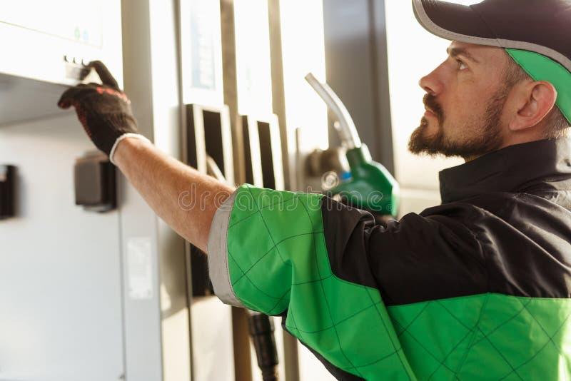 De duwende knopen van de benzinestationwerknemer op pomp stock afbeelding