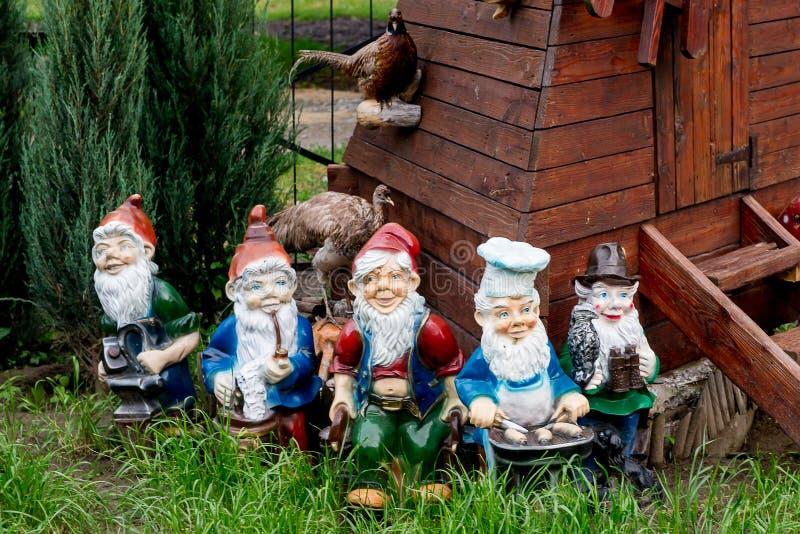 De dwergen verfraaien de tuin dichtbij het huis Beeldhouwwerken fabelachtige dwergen stock foto's
