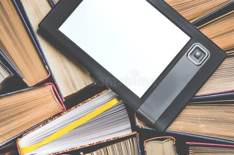 De e-book met het wit scherm ligt op de open multi-colored boeken die op een donkere achtergrond, close-up liggen royalty-vrije stock afbeeldingen