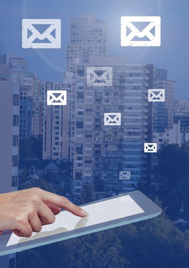 De e-mailpictogrammen van de holdingstablet en over stad royalty-vrije stock fotografie