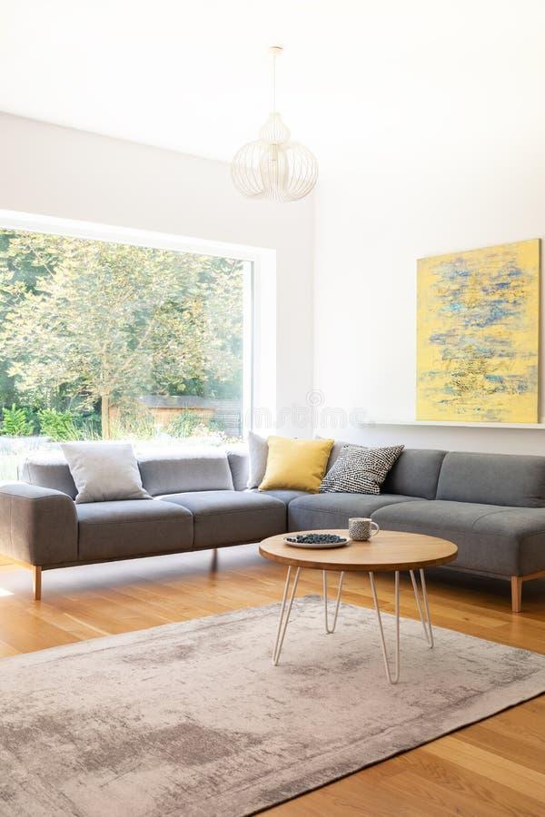 De echte foto van haarspeldkoffietafel met bosbessen op plaat en de thee overvallen status op tapijt in Skandinavische stijlwoonk stock foto