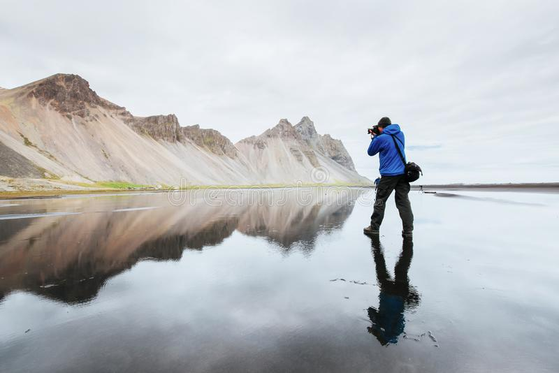 De echtgenoot is een fotograaf die zich op de waterspiegel bij de kust van IJsland in Stokksnes bevinden stock foto's