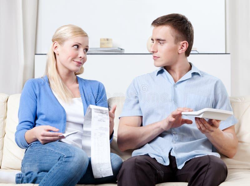 De echtgenoot en de vrouw berekenen de uitgaven stock afbeeldingen