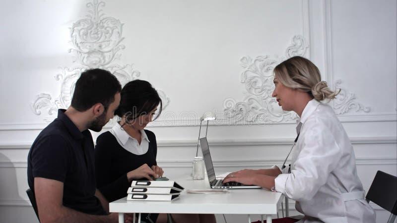 De echtgenoot en de vrouw kwamen voor overleg aan de arts in het bureau royalty-vrije stock afbeeldingen