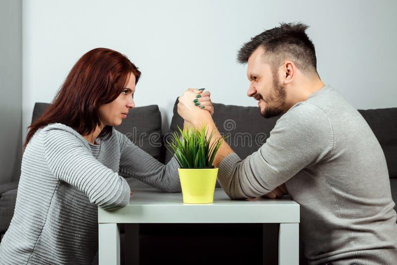 De echtgenoot en de vrouw vechten in hun wapens, wapen die tussen mannetje en wijfje worstelen Familieruzie, krachtmeting, afdeli stock afbeelding