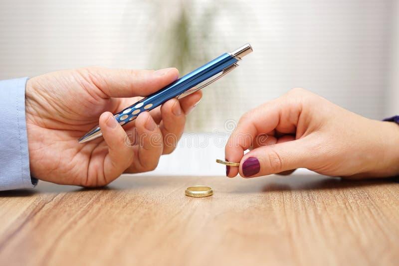 De echtgenoot geeft achterin pen aan de documenten van de tekenscheiding zijn vroegere vrouw stock afbeeldingen