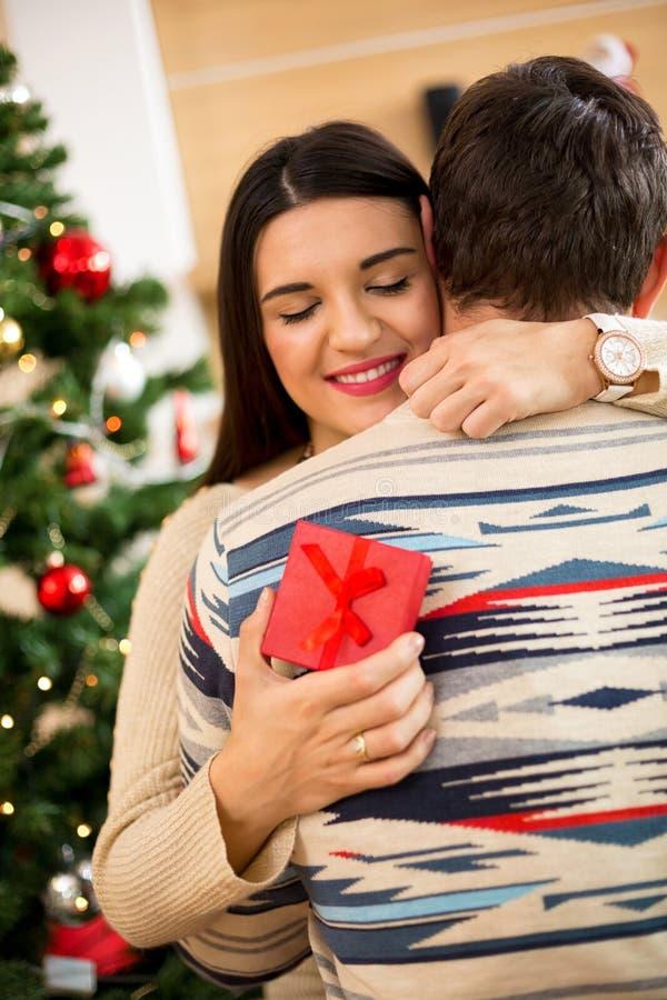 De echtgenoot geeft een heden aan zijn mooie vrouw voor een Kerstmisholida stock foto's
