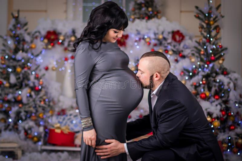 De echtgenoot kust buik zwangere vrouw bij Kerstmis stock fotografie