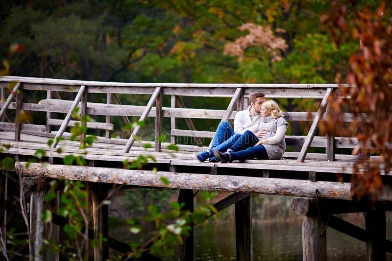 De echtgenoot kust zijn zwangere vrouwenzitting op een houten brug royalty-vrije stock foto