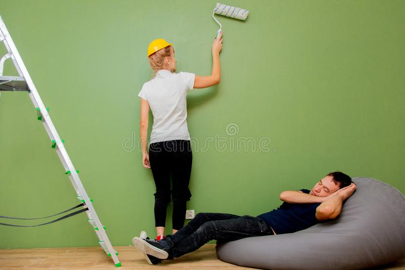 De echtgenoot slaapt terwijl de vrouw de muur in groen schildert royalty-vrije stock afbeelding