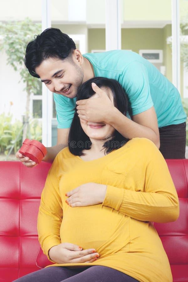 De echtgenoot verrast zwangere vrouw met gift royalty-vrije stock afbeelding