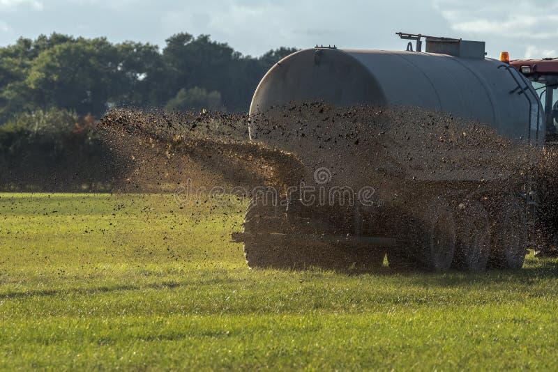 De een landbouwbedrijftractoren bespuit mest stock afbeeldingen
