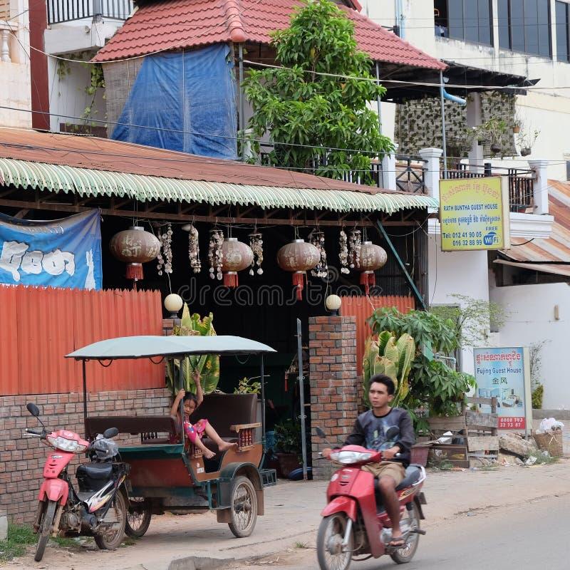 De een weinig Aziatische meisjesspelen in een motorriksja, een autoped berijdt langs de weg stock afbeeldingen
